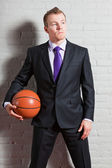 Fotografie Business man with basketball. Good looking young man with short blond hair. Gym indoor.