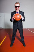 Fotografie Angry business man with basketball. Wearing dark sunglasses. Good looking young man with short blond hair. Gym indoor.