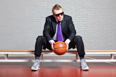 Business man with basketball. Wearing dark sunglasses. Good looking young man with short blond hair. Sitting on bench in gym indoor. stock vector