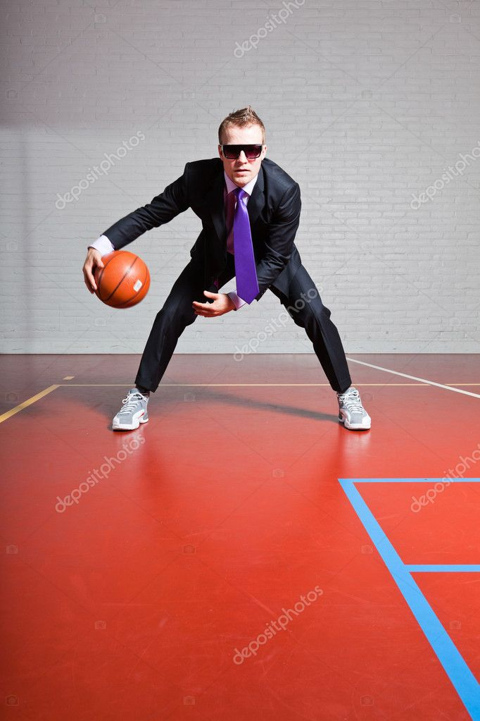 Business man with basketball. Wearing dark sunglasses. Good looking young man with short blond hair. Gym indoor.
