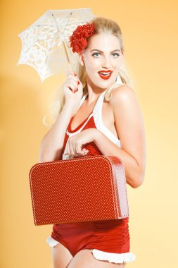 Sexy blonde pin up girl wearing red swimwear holding a little suitcase and white umbrella. Retro style. Fashion studio shot isolated on yellow background.