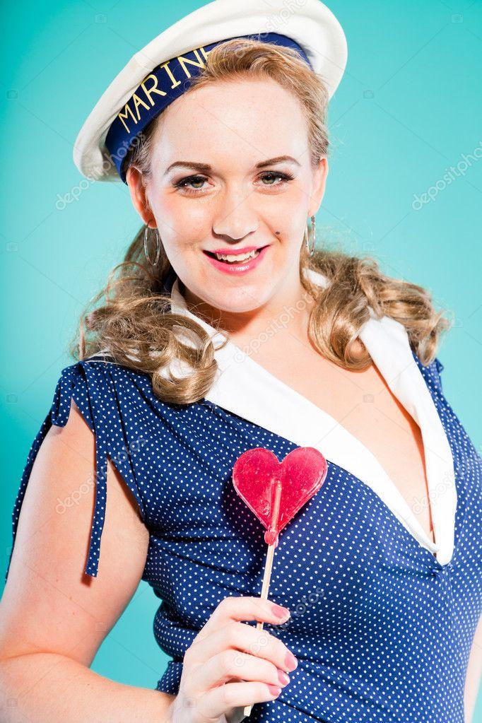 afb18fb2e346 Sexy bionda pin la ragazza indossa un abito blu con puntini bianchi e  marino cap. lecca-lecca rosa in mano. stile retrò. studio moda colpo  isolato su sfondo ...