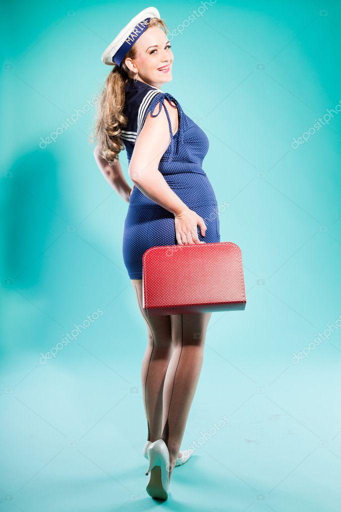pin rubia sexy chica vestido azul con puntos blancos y gorra de marino.  sosteniendo la maleta roja vintage. estilo retro. estudio de moda disparo  aislado ... 0fec2cf4d69