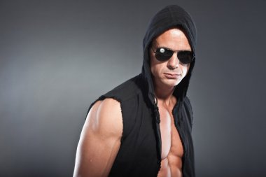 Muscled fitness man. Cool looking. Tough guy. Blue eyes. Blond short hair. Wearing black hoody shirt and sunglasses. Tanned skin. Studio shot isolated on grey background.
