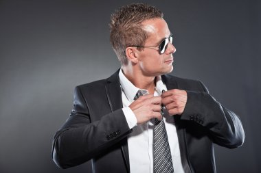 Good looking business man with black sunglasses and short blond hair. Tough guy. Wearing tie and black jacket.
