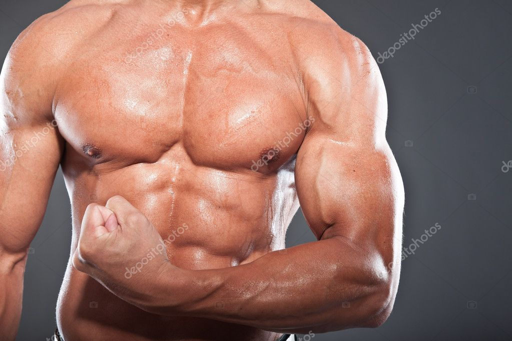 Closeup of shirtless muscled fitness man. Tough guy. Tanned skin. Studio shot isolated on grey background.