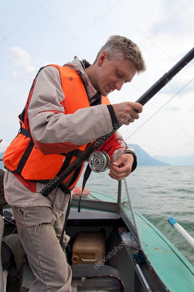 A fisherman wearing a life jacket.