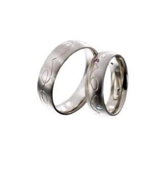 A pair of wedding rings set with colorful diamonds on white background