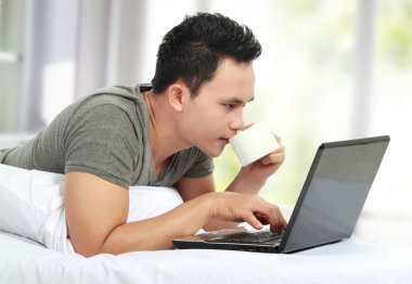 Man lying on a bed and using a laptop computer