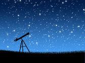dalekohled na trávě pod hvězdami
