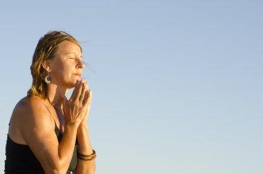 Pretty woman praying and meditating at sunset