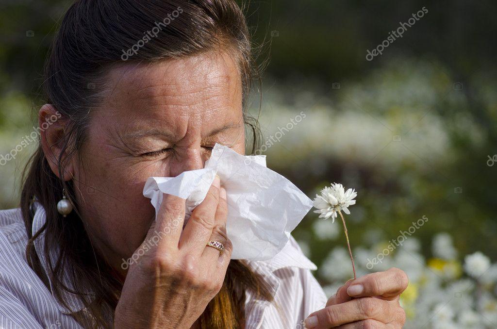 Woman suffering hay fever in field of wildflower
