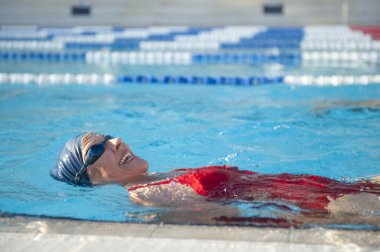 Active Senior woman swimming in pool