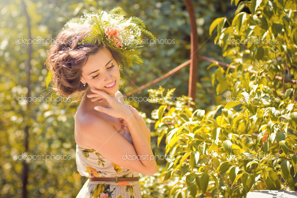 A beautiful girl in a light dress with flowers in the park