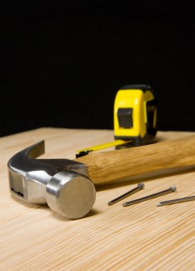 Hammer and tape measure on wood