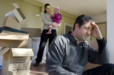 Upset young parents and their daughter outside their home