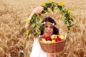 Lány tart kosár gyümölcs, a mező a búza