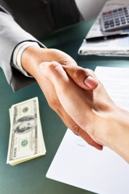 Two handshaking, taken close up against glass table, with stacks of dollar bills on table stock vector