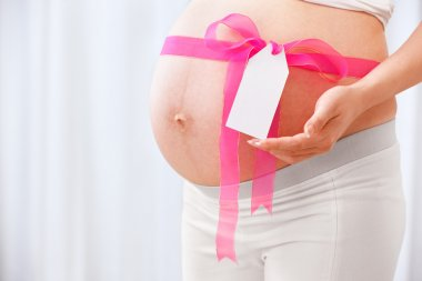 Pink ribbon arround pregnant lady's stomach