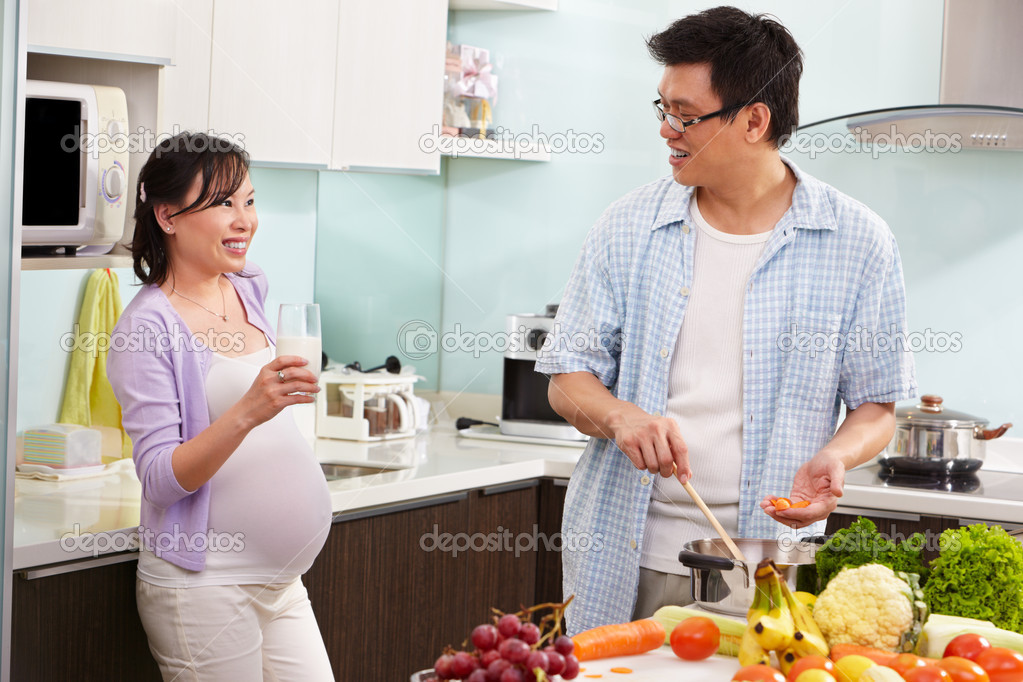 Pregnant wife drinking milk watching her husband — Stock ...