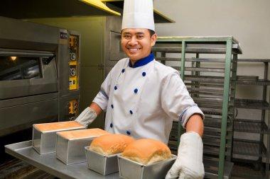 Baker holding fresh bread from oven