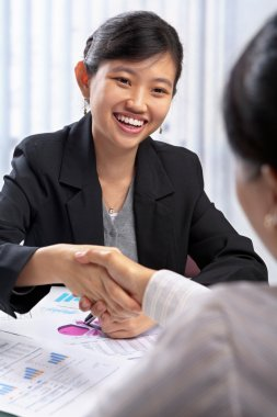 Chinese busineswoman handshake with her client