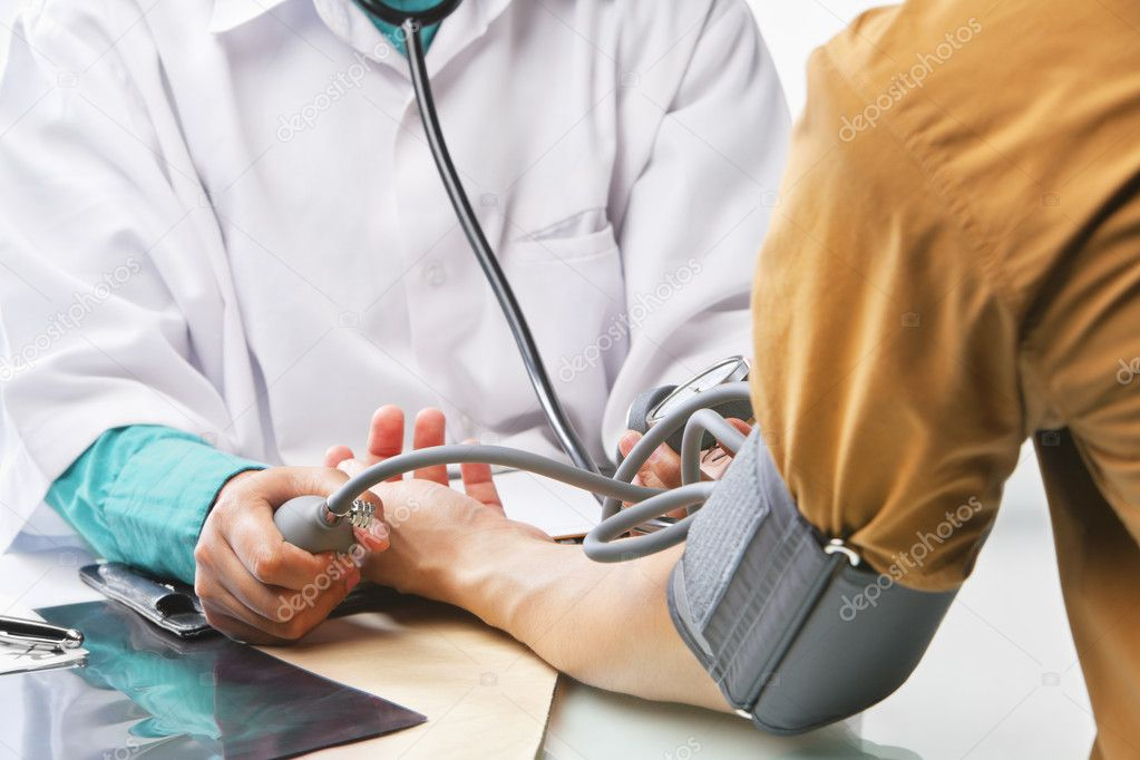 Doctor checking patient's blood presure, focus on the hand