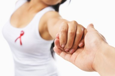 Woman holding hand to give support for AIDS cause or breast canc