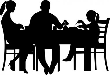 Family having their dinner at the table silhouette
