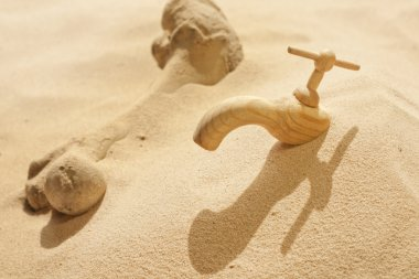 Global warming climate change faucet in the sand