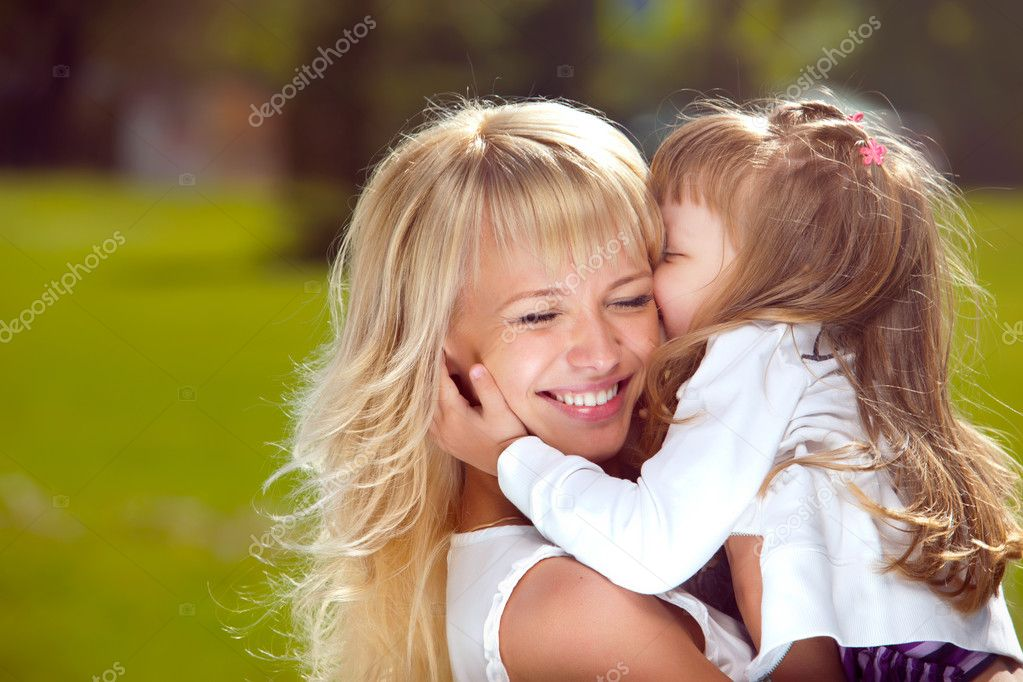 Mother holds her daughter in her arms