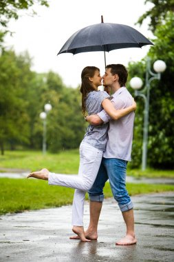 Photo of romantic barefooted couple standing on the road in rain and going to kiss each other stock vector