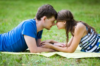 Happy woman and her boyfriend resting on green lawn in park