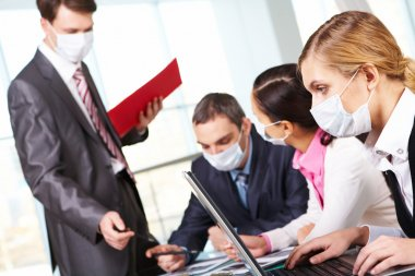 Serious businesswoman in protective mask looking at screen of laptop in working environment stock vector