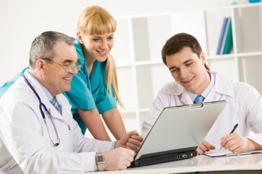Group of therapists looking at laptop screen and discussing new method of treatment stock vector