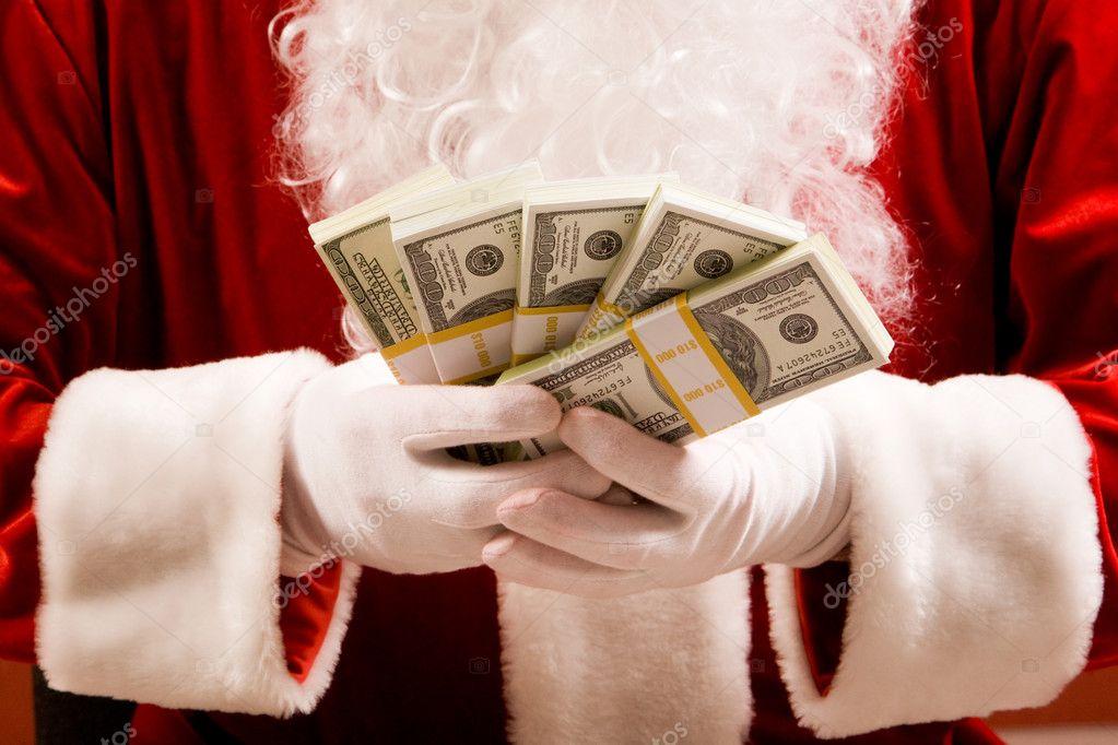 Close-up of Santa hands with stacks of dollar banknotes