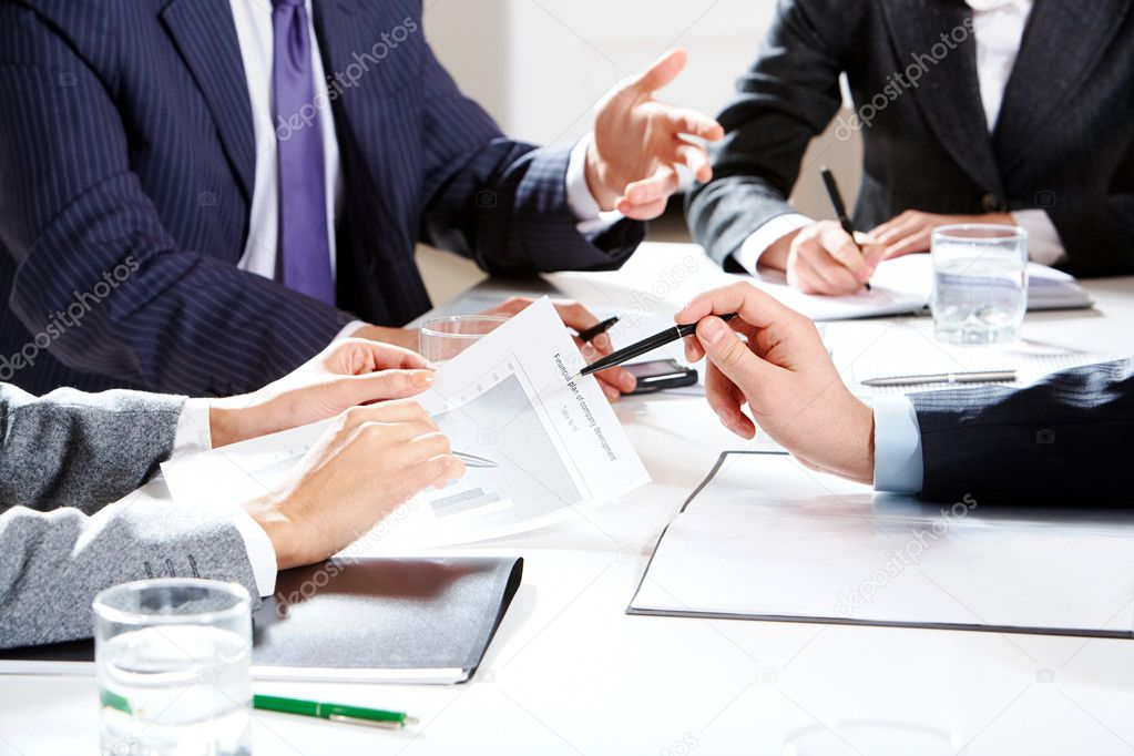 Close-up of businessman hand with pen explaining a financial plan to colleagues at meeting