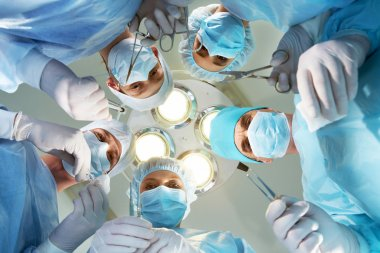 Below view of surgeons holding medical instruments in hands and looking at patient stock vector