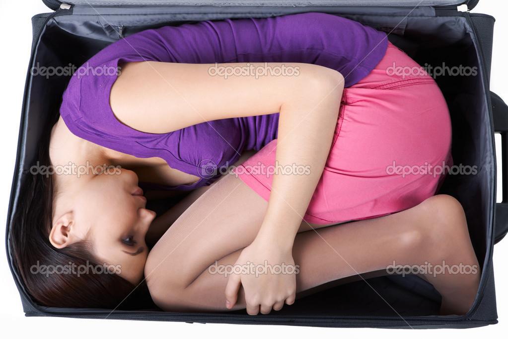 Photo of young woman lying in big suitcase