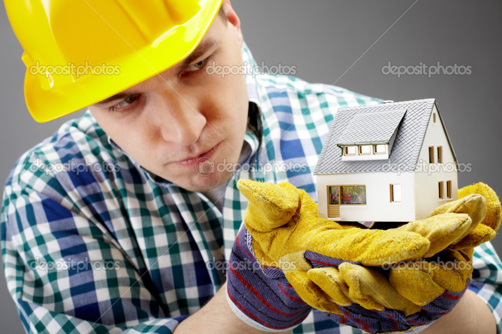 Portrait of a serious architect holding a house model and looking at it