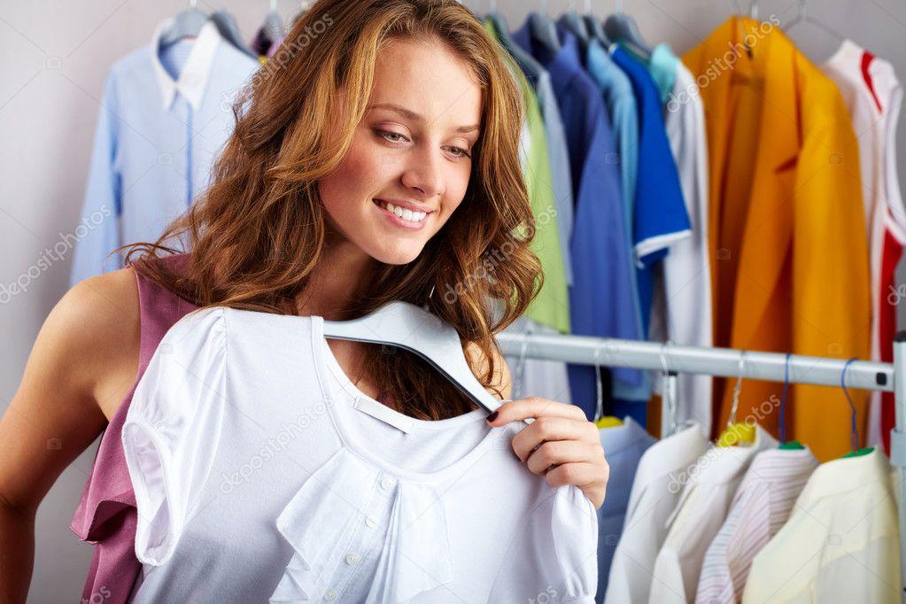 A girl choosing a t-shirt in the shop