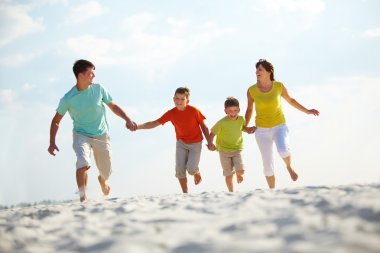 Photo of happy family running down the beach on summer stock vector