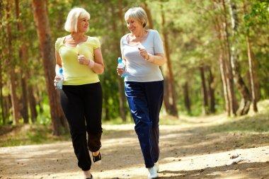 Portrait of two senior females running outdoors stock vector