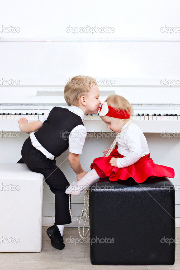 Little children sitting near piano