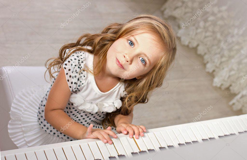Beautiful blond little girl in pretties sitting near a piano