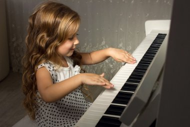 Blond girl playing a piano
