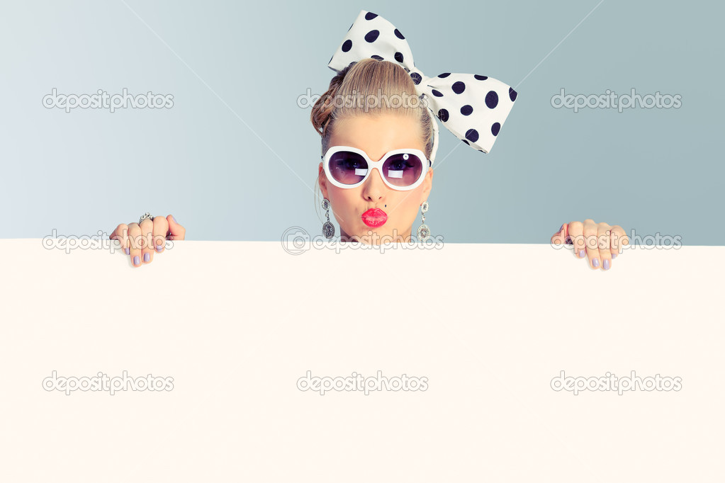 Beautiful young woman with pin-up make-up and hairstyle posing in studio with white board. stock vector