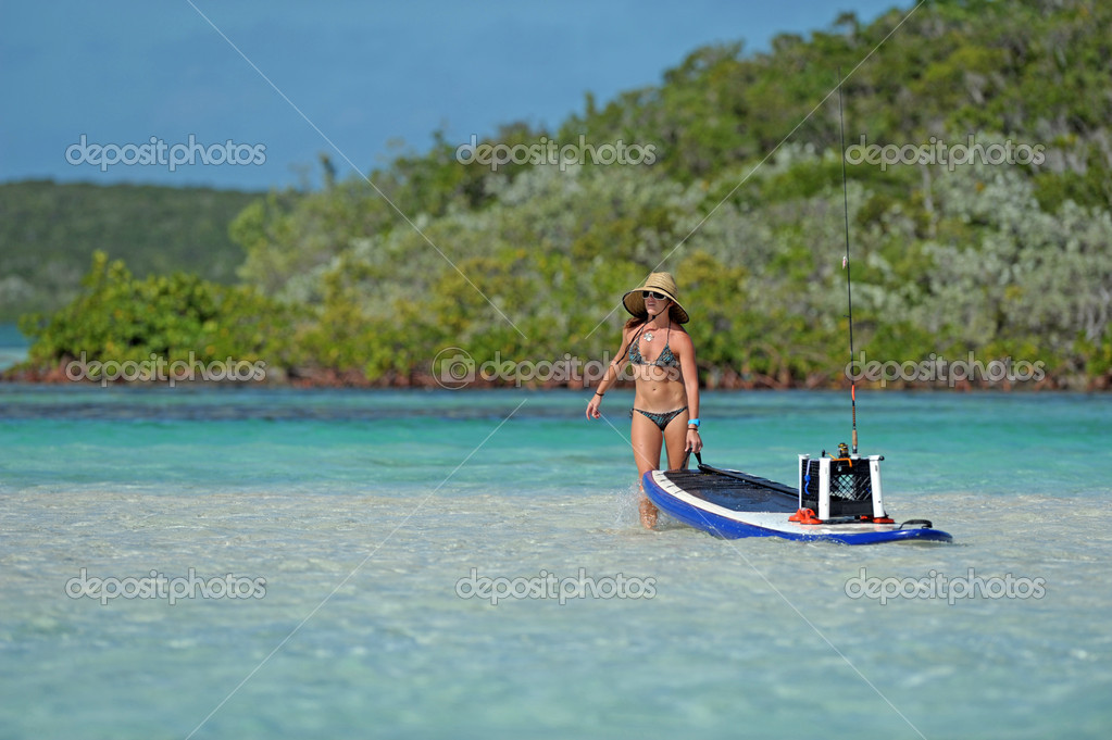 Woman pulling paddle board out to sea