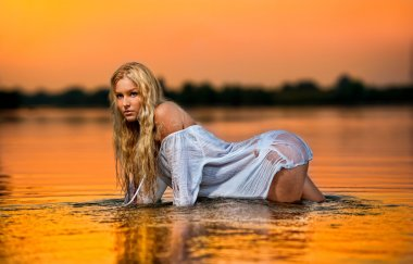 Sexy blonde woman in water at sunset .Beautiful swimsuit model in the water