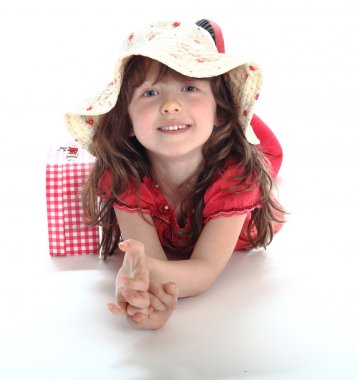The little girl lies in a hat and smiles